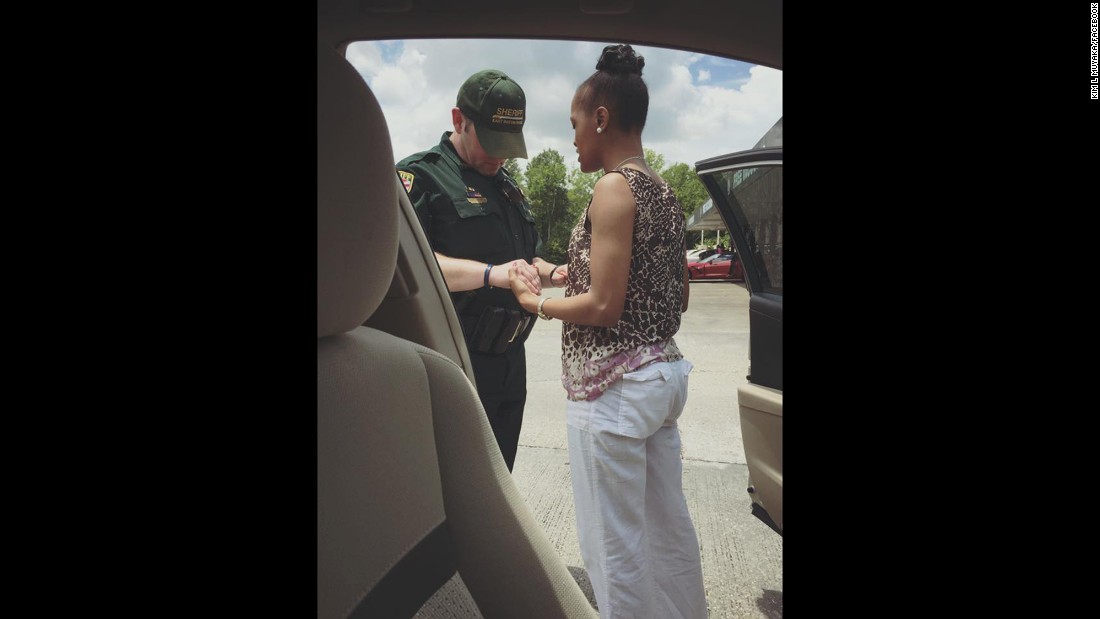 "Kim Muyaka -- head bowed, eyes closed, hands tightly entwined with those of an East Baton Rouge police officer -- prays that God would ""cover this Police Officer ... and use his hands not to hurt or harm but to protect the citizens."" Muyaka posted this now-viral photo to her Facebook page."