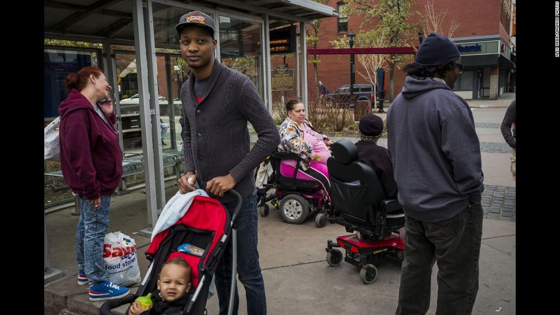 People wait for buses in Ohio City, an increasingly racially mixed neighborhood.