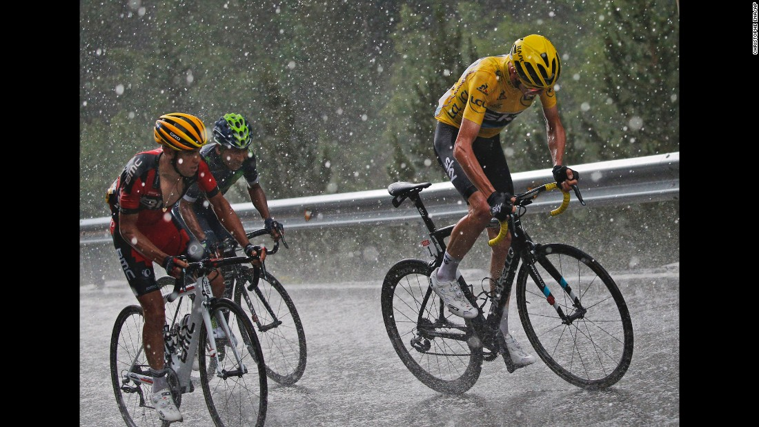 Britain's Chris Froome, wearing the overall leader's yellow jersey, Australia's Richie Porte, in red, and Colombia's Nairo Quintana, in green, climb a hill in the rain, hail and lightning during the ninth stage of the Tour de France on Sunday, July 10.