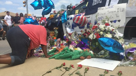 Djuana Franklin prays for the Dallas officers killed at a memorial.