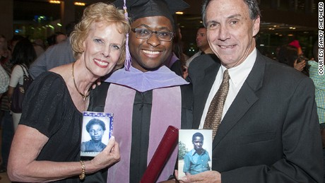 Given Kachepa at his graduation, with foster parents Sandy and Deetz Shepherd, who are holding photos of Kachepa's birth parents.