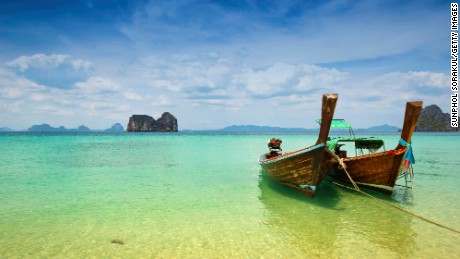 Two wooden longtail boats mooring on the beach with limestone rock formation in the background, Trang, South of Thailand.
