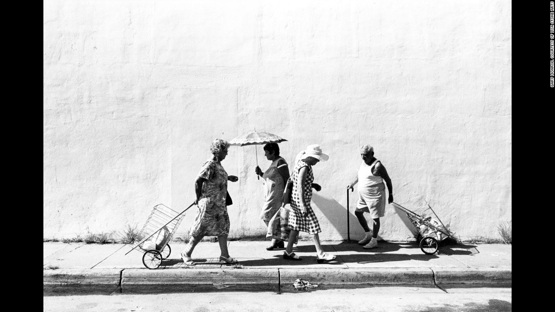 """People walk along Sixth Street, off Washington Avenue, in 1978. The South Beach the photographer shows us -- from 1977 through 1986 -- is a much different place than the one we know today. Monroe's images take us into the lives of the elderly Jewish community at the time, many of whom were survivors of the Holocaust and Czarist pogroms -- organized massacres of Jewish people. """"I didn't work with an agenda,"""" Monroe said. """"I was giving form to my intuitions, making photographs on a deep breath and a prayer, so to speak."""""""