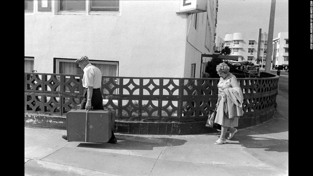 """A couple walks with their luggage at 15th Street and Ocean Drive in 1981. """"More recently I've taken to the old couple walking seemingly aimlessly across the sidewalk,"""" Monroe said about this image. """"He's carrying the weight of the luggage and the world, while his wife (one assumes) walks about 10 feet behind him. It's a quiet but poignant image."""""""