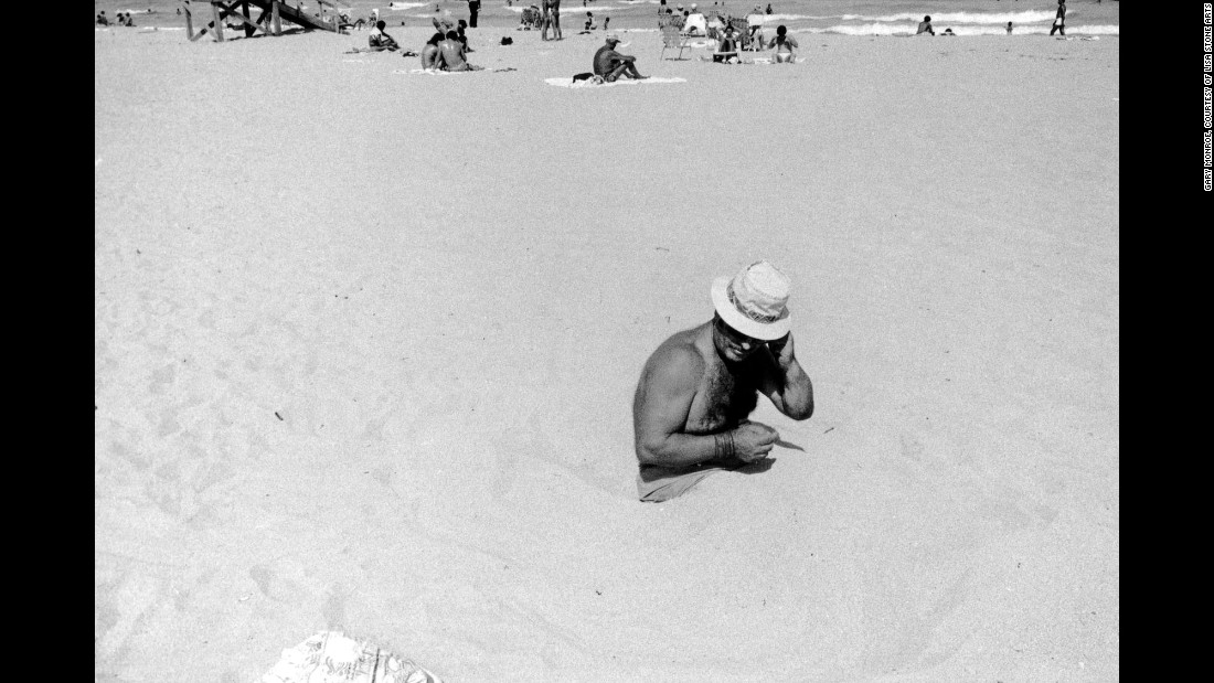 """A man sits in the sand at the Lummus Park beach in 1980. Although Monroe made thousands of prints, he selected only a few to include in his """"<a href=""""http://www.lisastonearts.com/gallery-store.html"""" target=""""_blank"""">Life in South Beach</a>"""" photo book. """"For whatever reason, I choose 18 because in Hebrew, the expression (often a toast) means 'to life,' """" he said. """"And I wanted to underscore, no matter how subtly, that idea. These people faced the worst of humanity and still, in old age even, lived life fully, with zest and optimism."""""""