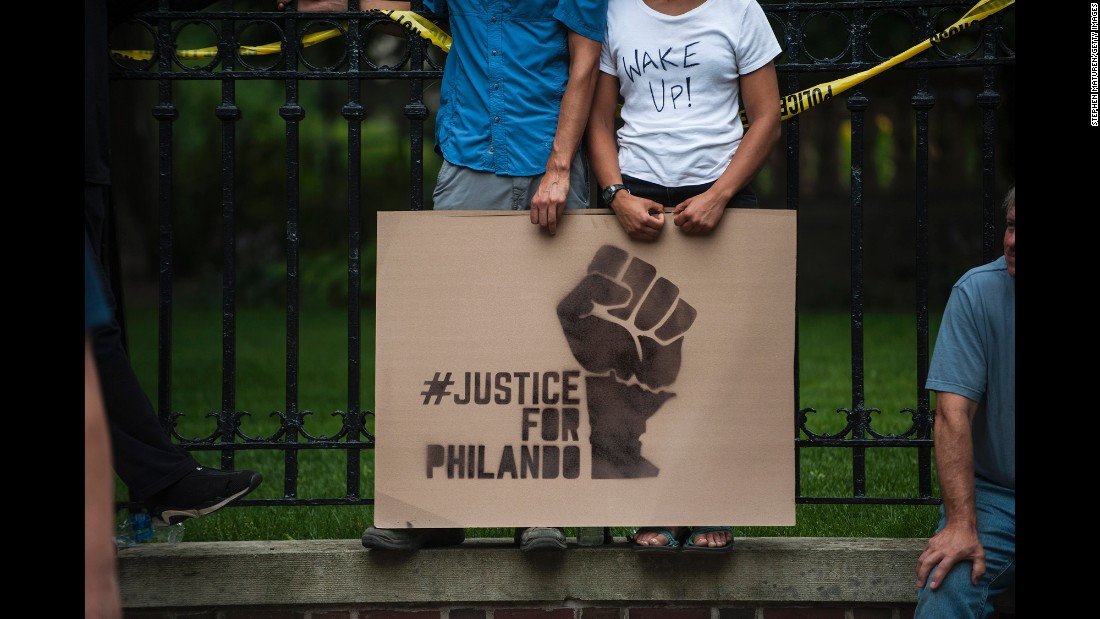 "A couple hold a sign protesting the <a href=""http://www.cnn.com/2016/07/07/us/falcon-heights-shooting-minnesota/"" target=""_blank"">killing of Philando Castile</a> outside the governor's mansion on July 7, in St. Paul, Minnesota. Castile's death was live-streamed by his fiancée and quickly went viral."