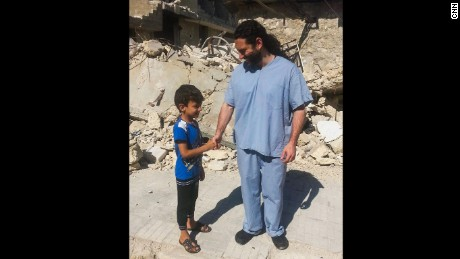 Dr. Samer Attar meeting one of the children who live in the bomb ravaged city.