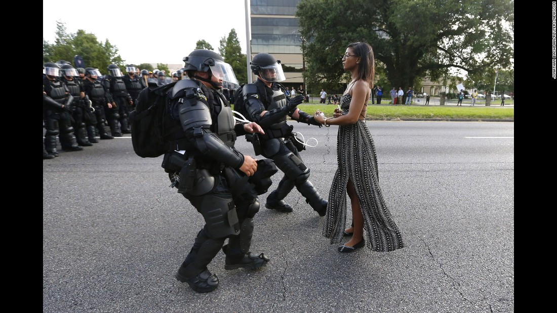 """A young woman stands in the street as two police officers move in to arrest her near the headquarters of the Baton Rouge Police Department in Louisiana on Saturday, July 9. She was one of hundreds of protesters who blocked a Baton Rouge roadway during <a href=""""http://www.cnn.com/2016/07/09/us/black-lives-matter-protests/"""" target=""""_blank"""">demonstrations against police brutality</a> after the fatal shootings of two African-American men, one in Baton Rouge. Some have said this image, taken by Jonathan Bachman for Reuters, has come to <a href=""""http://www.cnn.com/2016/07/11/us/baton-rouge-protester-photograph/"""" target=""""_blank"""">symbolize the week's protests</a>."""