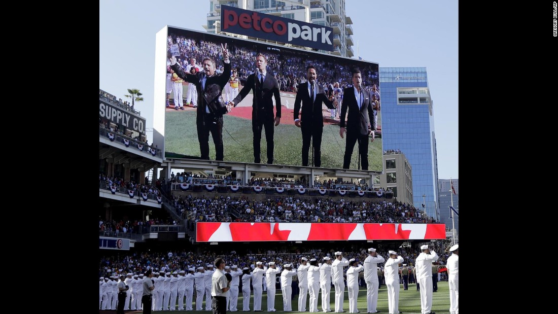 """The Tenors, shown on the scoreboard, perform the Canadian National Anthem before the MLB All-Star Game in San Diego on Tuesday, July 12. A member of the Canadian singing quartet changed a lyric in the anthem and held up a sign proclaiming """"All Lives Matter"""" during a pregame performance."""
