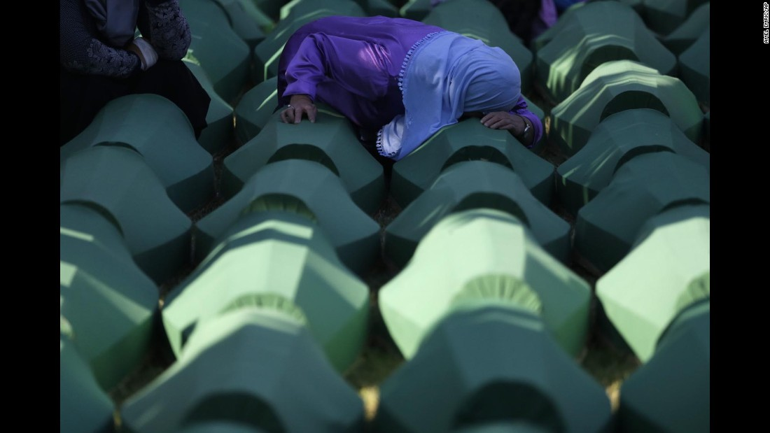 """A Bosnian woman prays next to a coffin containing the remains of a relative who perished in the <a href=""""http://www.cnn.com/2015/07/11/europe/srebrenica-massacre-bosnians/"""" target=""""_blank"""">Srebrenica massacre</a> -- the genocidal killing of more than 8,000 Bosniaks during the Bosnian War in July 1995 -- during a funeral near Srebrenica on Monday, July 11."""