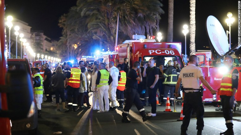 """Police officers, firefighters and rescue workers are seen at the site of an attack on July 15, 2016, after a truck drove into a crowd watching a fireworks display in the French Riviera town of Nice. A truck ploughed into a crowd in the French resort of Nice on July 14, leaving at least 60 dead and scores injured in an """"attack"""" after a Bastille Day fireworks display, prosecutors said on July 15.  / AFP / Valery HACHE        (Photo credit should read VALERY HACHE/AFP/Getty Images)"""