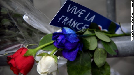 "A sign reading ""Long live France"" is placed near roses in the colors of the French flag at a makeshift memorial in front of the French Embassy in Rome on July 15, 2016, in honour of the victims of an attack in Nice, France."