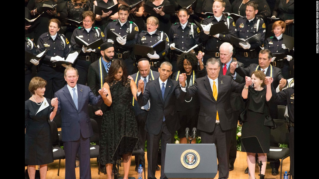 """U.S. first lady Michelle Obama and President Barack Obama, with, from left, former first lady Laura Bush, former President George W. Bush,  Dallas Mayor Mike Rawlings and his wife, Micki Rawlings, at an interfaith memorial service in Dallas on Tuesday, July 12, after the <a href=""""http://www.cnn.com/2016/07/08/us/philando-castile-alton-sterling-protests/index.html"""" target=""""_blank"""">killings of five police officers</a> during an anti-police brutality protest in the city just days before."""