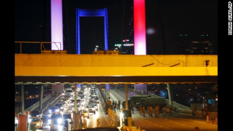 """Turkish soldiers block Istanbul's iconic Bosporus Bridge on Friday, July 15, 2016, lit in the colours of the French flag in solidarity with the victims of Thursday's attack in Nice, France. A group within Turkey's military has engaged in what appeared to be an attempted coup, the prime minister said, with military jets flying over the capital and reports of vehicles blocking two major bridges in Istanbul. Prime Minister Binali Yildirim told NTV television: """"it is correct that there was an attempt,"""" when asked if there was a coup."""