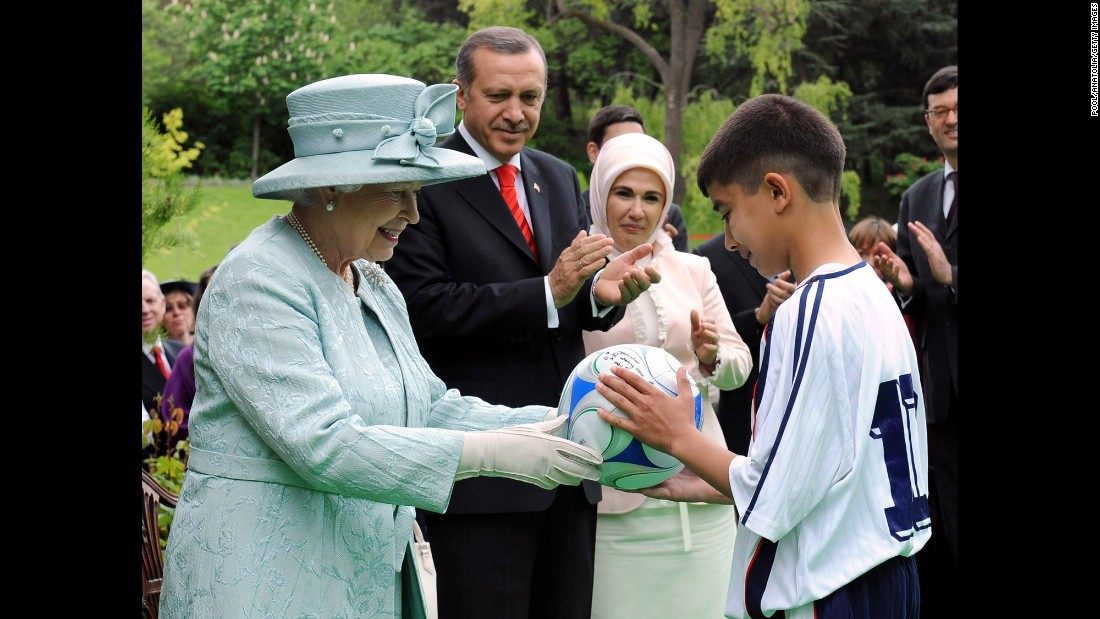 Britain's Queen Elizabeth II, accompanied by Erdogan and his wife Emine Erdogan, gives a David Beckham signed soccer ball to a Turkish boy during at a garden party held for her birthday at the British Embassy in Ankara, Turkey, on May 16, 2008. It was the Queen's first visit to Turkey in 37 years.