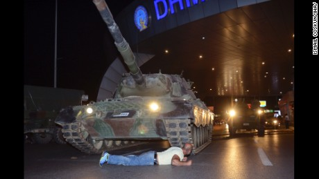 A man lays in front of a tank at the entrance to Istanbul Ataturk Airport.