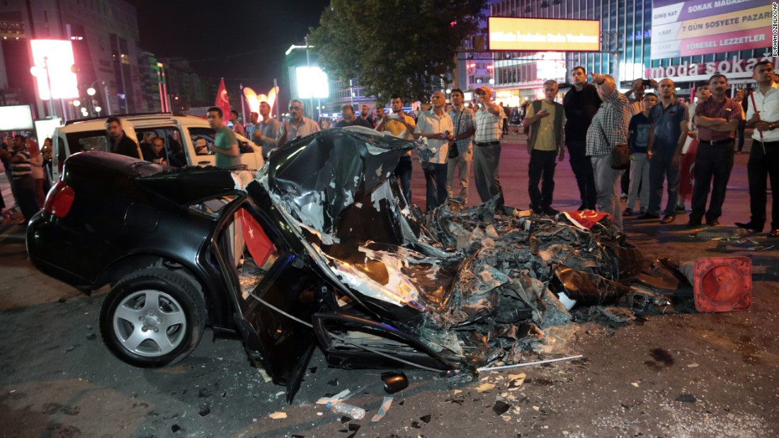 People gather around a car damaged by a tank in Kizilay Square early on July 16.