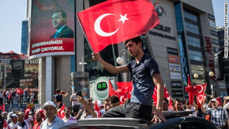 A man waves a Turkish flag from the roof of a car during a march around Kizilay Square in reaction to the attempted military coup on Saturday July 16 in Ankara, Turkey.
