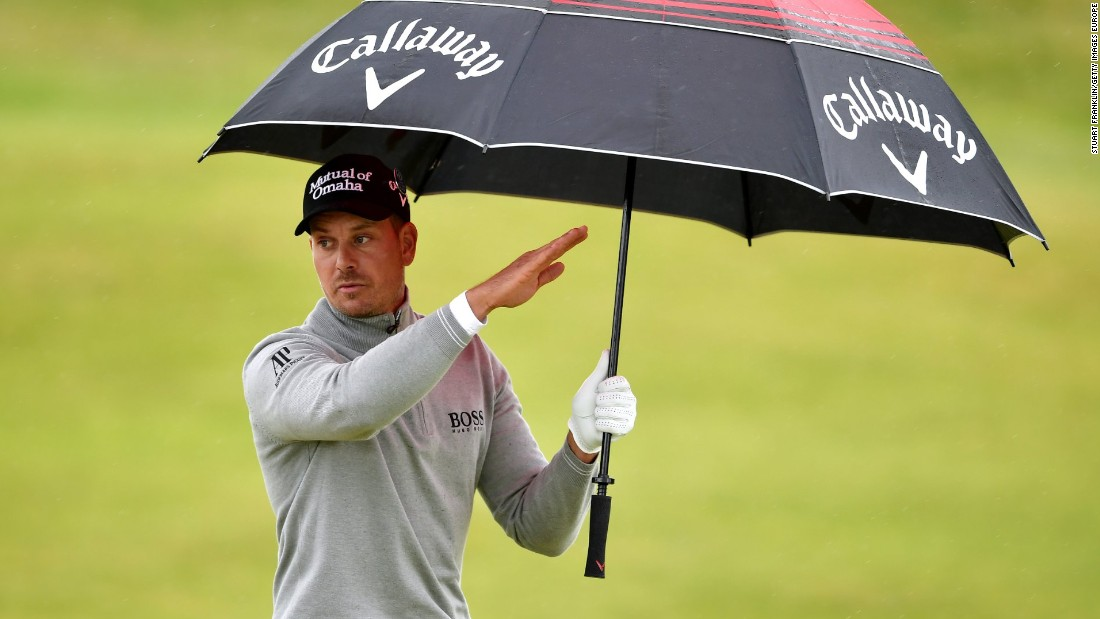 Stenson takes shelter from the intermittent showers on the third day.