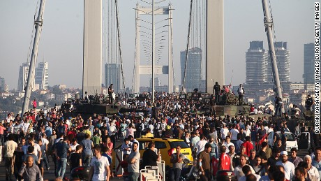 ISTANBUL, TURKEY - JULY 16: People gather for celebration around Turkish police officers, loyal to the government, standing atop tanks abandoned by Turkish army officers, against a backdrop of Istanbul's iconic Bosporus Bridge on July 16, 2016 in Istanbul, Turkey. Istanbul's bridges across the Bosphorus, the strait separating the European and Asian sides of the city, have been closed to traffic.Turkish President Recep Tayyip Erdogan has denounced an army coup attempt, that has left  has left high fatalities and thousands injured in overnight clashes in Istanbul and Ankara.  (Photo by Burak Kara/Getty Images)