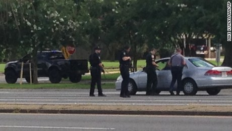 Authorities talk to the driver of a car near an area where several officers were shot while on duty less than a mile from police headquarters, Sunday, July 17, 2016, in Baton Rouge, La. (AP Photo/Mike Kunzelman)