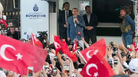 """Turkish President Recep Tayyip Erdodan (C) speaks during a rally near his house in Istanbul on July 16, 2016 after Turkish authorities wrested back control of the Ataturk airport.  President Recep Tayyip Erdogan urged Turks to remain on the streets on July 16, 2016, as his forces regained control after a spectacular coup bid by discontented soldiers that claimed more than 250 lives. Describing the attempted coup as a """"black stain"""" on Turkey's democracy, Yildirim said that 161 people had been killed in the night of violence and 1,440 wounded. / AFP / GURCAN OZTURK        (Photo credit should read GURCAN OZTURK/AFP/Getty Images)"""