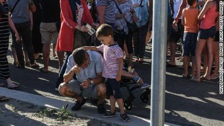 A young boy comforts his father Saturday on the Promenade des Anglais in Nice.