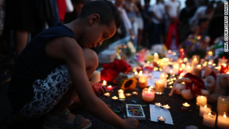 NICE, FRANCE - JULY 15: A boy writes on the ground next to flowers placed on the Promenade des Anglais on July 15, 2016 in Nice, France. A French-Tunisian attacker killed 84 people as he drove a lorry through crowds, gathered to watch a firework display during Bastille Day Celebrations. The attacker then opened fire on people in the crowd before being shot dead by police. (Photo by Carl Court/Getty Images)