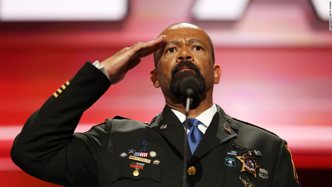 "Milwaukee County Sheriff David A. Clarke Jr. salutes the crowd before speaking Monday. He got huge applause when he started off his speech by saying, ""Blue lives matter!"""