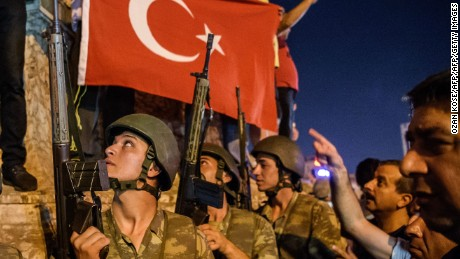 TOPSHOT - EDITORS NOTE: Graphic content / Turkish solders stay with weapons at Taksim square as people protest against the military coup in Istanbul on July 16, 2016.  Turkish military forces on July 16 opened fire on crowds gathered in Istanbul following a coup attempt, causing casualties, an AFP photographer said. The soldiers opened fire on grounds around the first bridge across the Bosphorus dividing Europe and Asia, said the photographer, who saw wounded people being taken to ambulances.   / AFP / OZAN KOSE        (Photo credit should read OZAN KOSE/AFP/Getty Images)