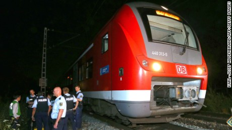 Police officers stand by a regional train in Wuerzburg southern Germany on July 18, 2016 after a man attacked train passengers with an axe.  German police killed the man after he attacked passengers on a train with an axe and a knife, seriously wounding three people, news agency DPA reported citing police.