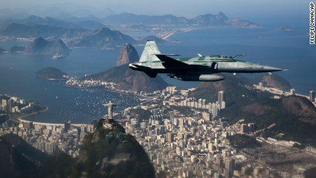 In this July 14, 2016 photo, a F-5 fighter flies over the Christ the Redeemer statue, Guanabara Bay and the Sugar Loaf mountain, photographed through a window, while intercepting another aircraft during a Brazilian Air Force presentation for the press ahead of the Olympic games in Rio de Janeiro, Brazil. (AP Photo/Felipe Dana)