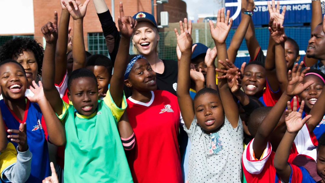 """Theron with children from<a href=""""http://www.whizzkidsunited.org/"""" target=""""_blank""""> WhizzKids United</a>, a youth project funded by her foundation, the <a href=""""http://charlizeafricaoutreach.org/"""" target=""""_blank"""">Charlize Theron Africa Outreach Project</a>."""