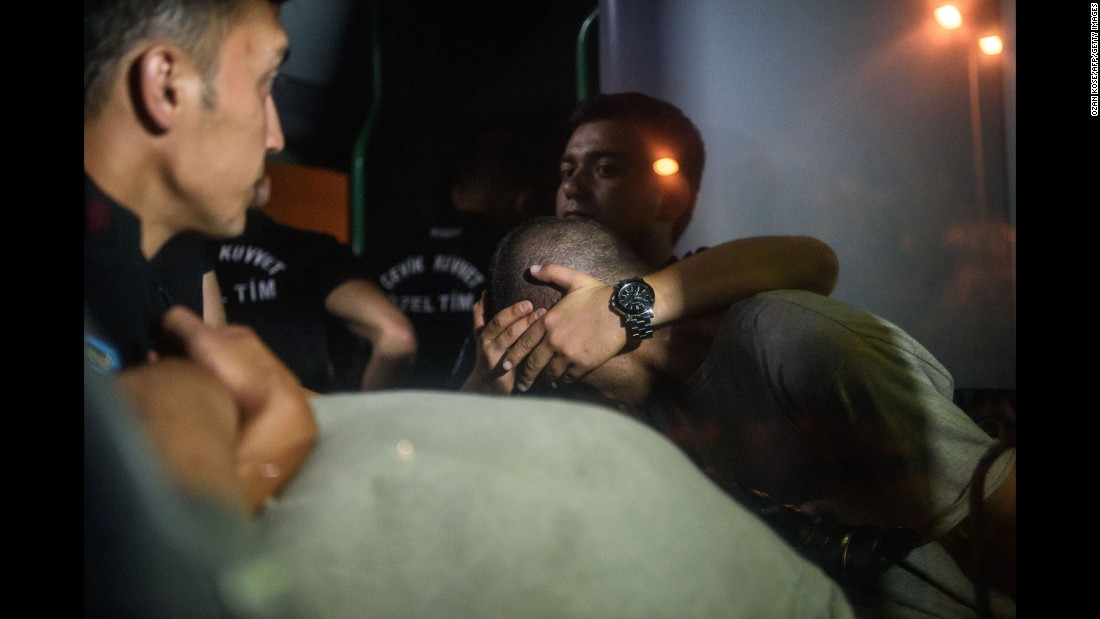 Turkish police officers cover the eyes of soldiers as they are transported in a bus from the courthouse in Istanbul on July 16.