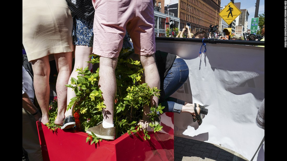 A woman climbs onto a plant stand outside the entrance to Quicken Loans Arena, the scene of the convention. The arena is home to LeBron James and the NBA champion Cleveland Cavaliers.