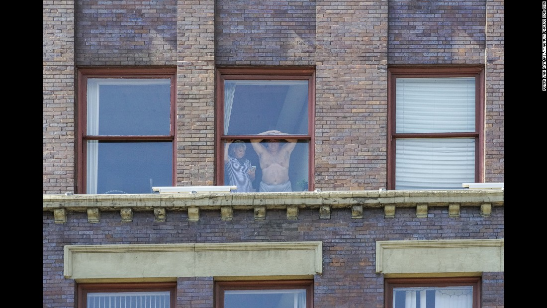 People watch the arrests from their window.