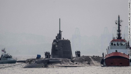 """A picture taken on July 20, 2016 in the port of Gibraltar shows the nuclear submarine HMS Ambush (C) making an unscheduled stop in Gibraltar due to a sustained damage to its conning tower after a """"glancing collision"""" with a merchant vessel."""