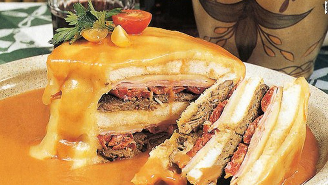 """Porto's favorite snack, francesinha -- or """"little French girl""""-- is bread filled with ham, sausages and steak, wrapped in cheese. The combo is then drenched in a spicy sauce."""