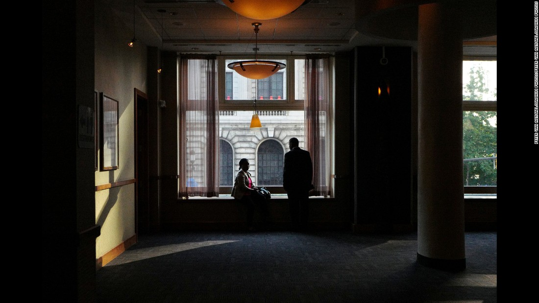 Two people take in the convention scene from a window in a bar.