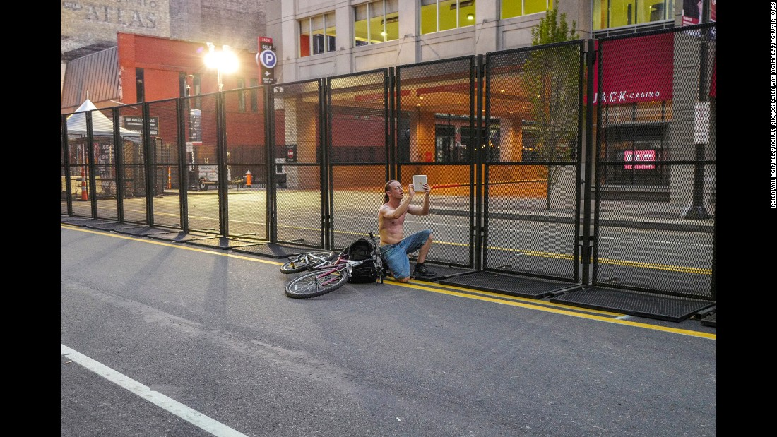 A man takes a photo outside the protective perimeter of the convention.