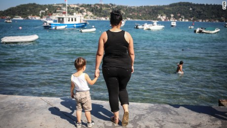 Damla, an unemployed high school dropout, hold's her son's hand as she poses for a photo next to the Bosphorous, in Istanbul.