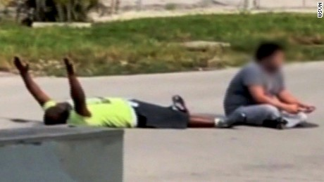 In cell phone footage, behavior therapist Charles Kinsey lies in the street with his hands in the air.