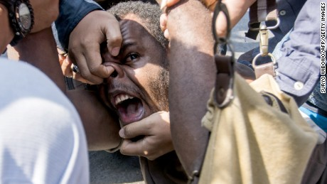 TOPSHOT - Papuan student Obi Kogoya screams as he is taken down by Indonesian police while trying to join a human rights protest at a Papuan student dormitory in Yogyakarta on July 15, 2016.
