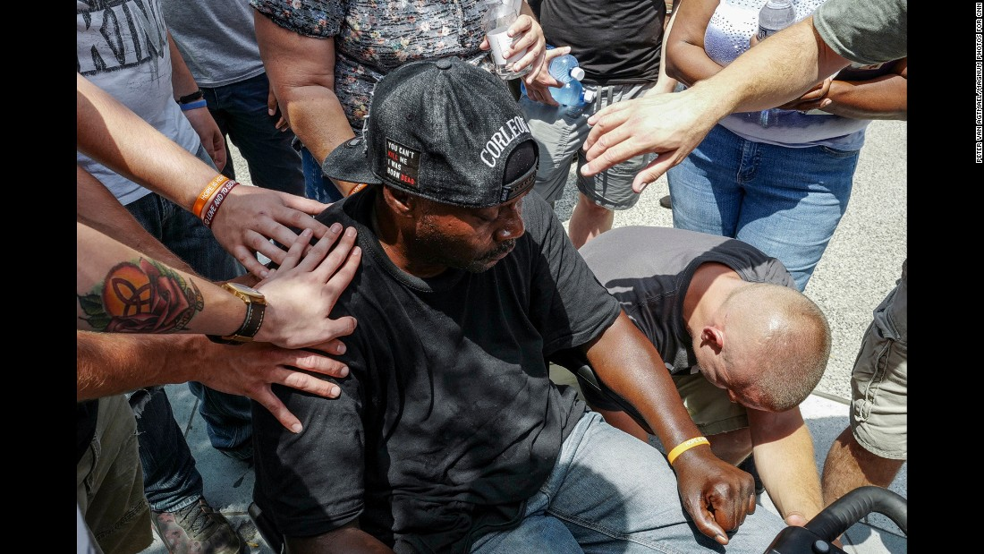 Members of a church group pray with a wheelchair-bound man and try to convince him that he will stand if he keeps praying with them.