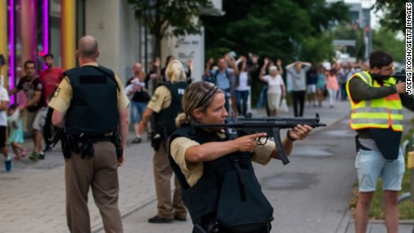Police officers escort people from inside the shopping center as they respond to a shooting at the Olympia Einkaufzentrum (OEZ) at July 22, 2016 in Munich, Germany.  According to reports, several people have been killed and an unknown number injured in a shooting at a shopping centre in the north-western Moosach district in Munich. Police are hunting the attacker or attackers who are thought to be still at large.