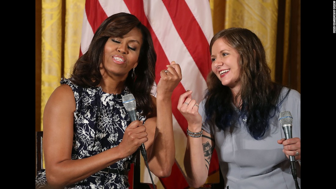 """First lady Michelle Obama snaps her fingers with student Rachel Scott at a White House event on Tuesday, July 19. The first lady was hosting the third-annual """"Beating the Odds"""" summit with more than 130 college-bound students."""