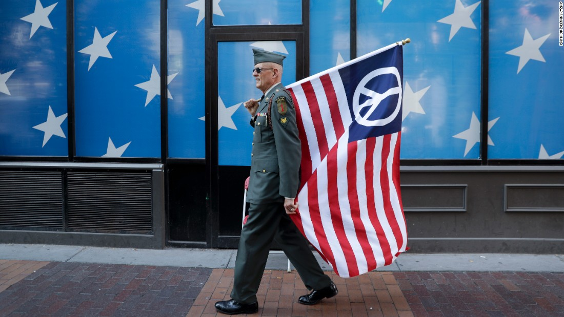 A protester carries a peace flag in downtown Cleveland on Sunday, July 17.