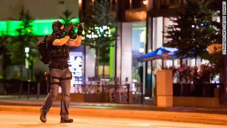 A policeman secures the area around the shopping mall Olympia Einkaufzentrum OEZ in Munich on July 22, 2016 after gunmen  went on a shooting rampage in the busy shopping centre, killing eight people in a suspected terror attack. 