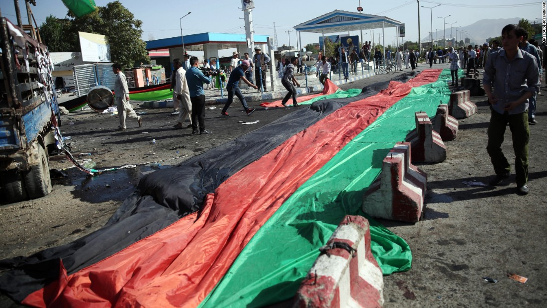 A banner in the colors of the Afghan flag is used to cover victim's blood after the deadly explosion.