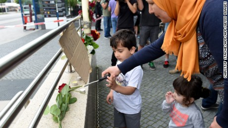 A veiled woman and her children lights candles to commemorate victims at the entrance of the subway station near the shopping mall Olympia Einkaufzentrum OEZ in Munich on July 23, 2016, a day after a gunman went on a shooting rampage, killing eight people in a suspected terror attack.  The southern city was in lockdown after the shootings, which saw panicked shoppers fleeing the Olympia mall as armed anti-terror police roamed the streets in search of assailant.  / AFP / Christof Stache        (Photo credit should read CHRISTOF STACHE/AFP/Getty Images)